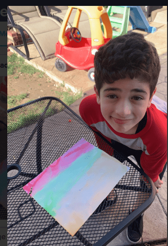 boy standing next to a painting