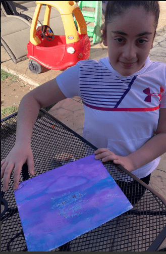 girl sitting next to a purple and blue painting
