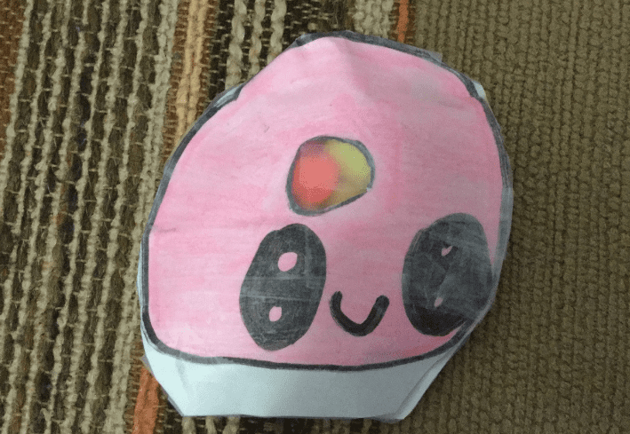paper cut and taped that is a round pink shape with black eyes and a smile