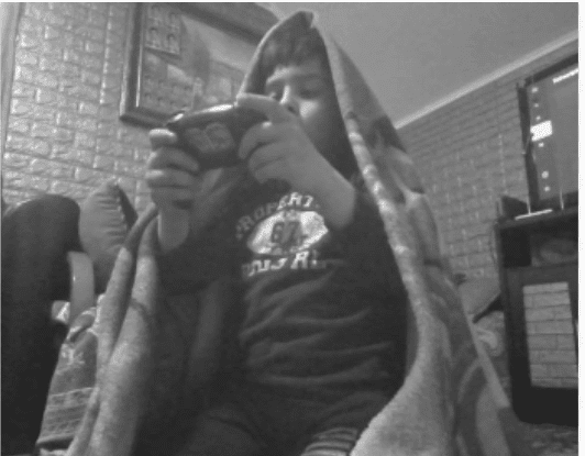 black and white photo of a boy playing a video game