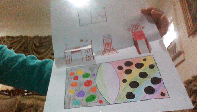 folded paper designed to look like the inside of a room- the chair and desk pop out and a colorful rug, window, and fireplace are drawn on the paper