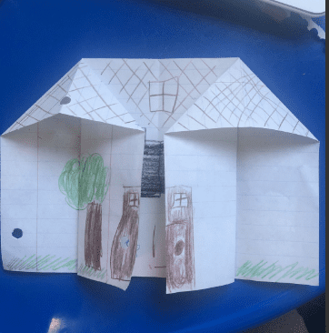 an oriami house with a door and tree drawn on it
