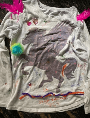 a shirt with a unicorn that has glitter, pipe cleaners, and feathers glued to it