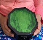 a painted hexagon box that is black and green