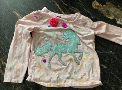 a painted unicorn short that has gems, and feathers glued to it