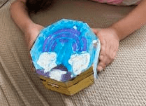 a hexagon box that has a purple rainbow, blue sky, and white clouds painted on it