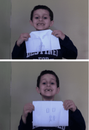 boy holding a white origami house