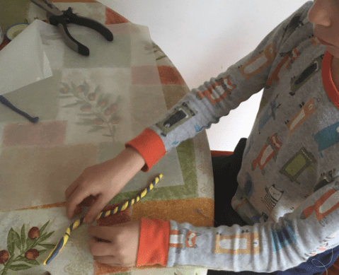 boy stisting two colored pieces of clay together