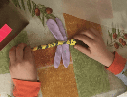 hands making a dragon fly out of clay