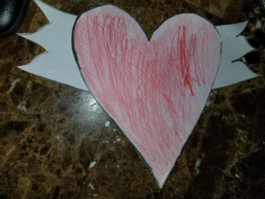 a red heart cut out with white wings on each side