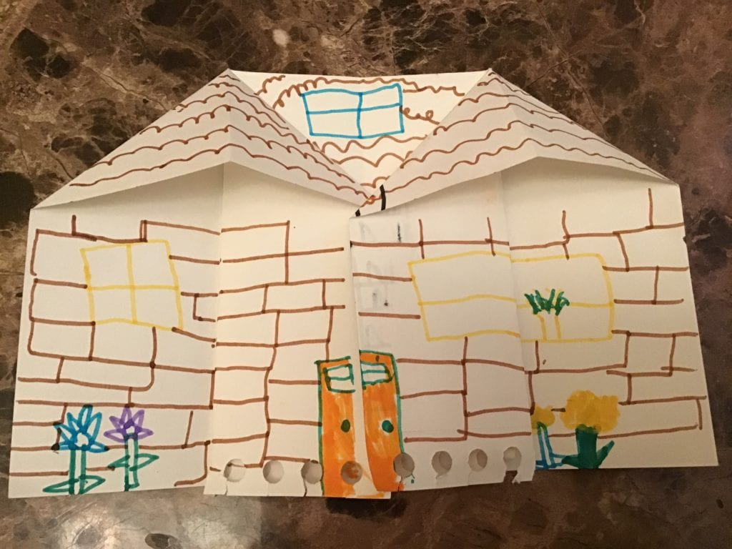 front of an origami house with brick, door, window, and flower details