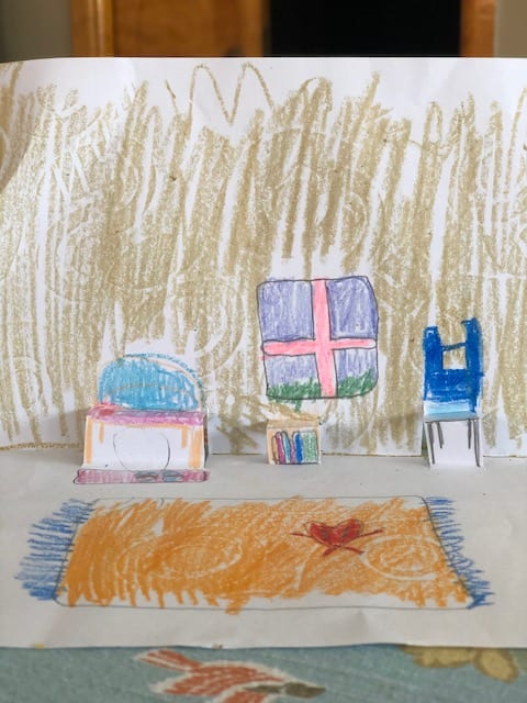 folded paper to look like a room with a pop out chair and desk and a rug and window drawn in the paper