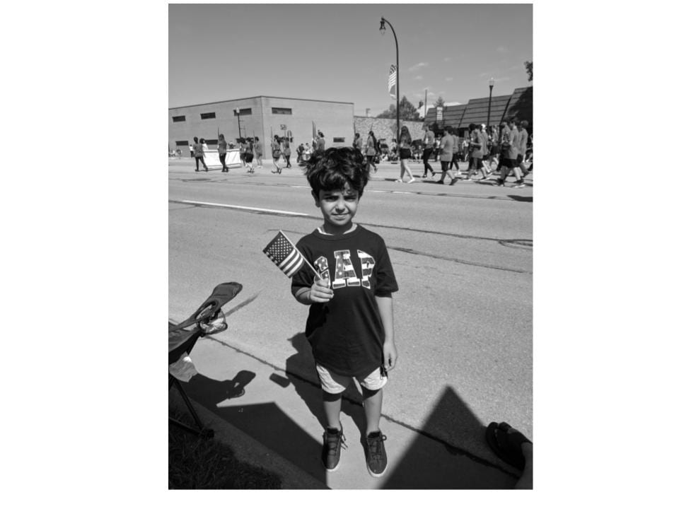 photo of a boy holding a flag at a parade that is black and white