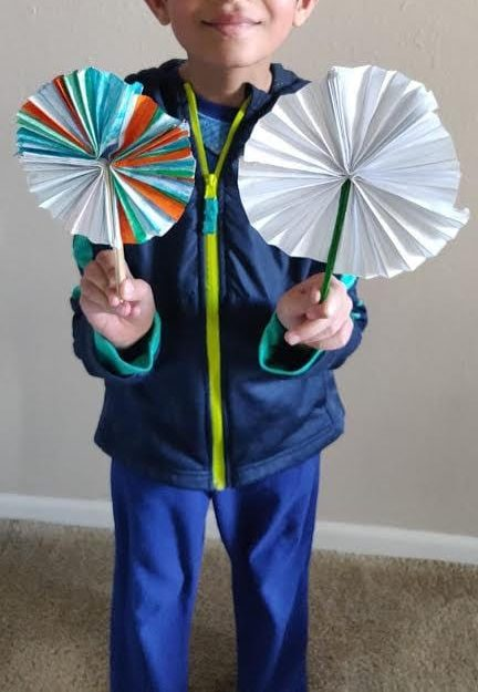 boy holding two paper fans