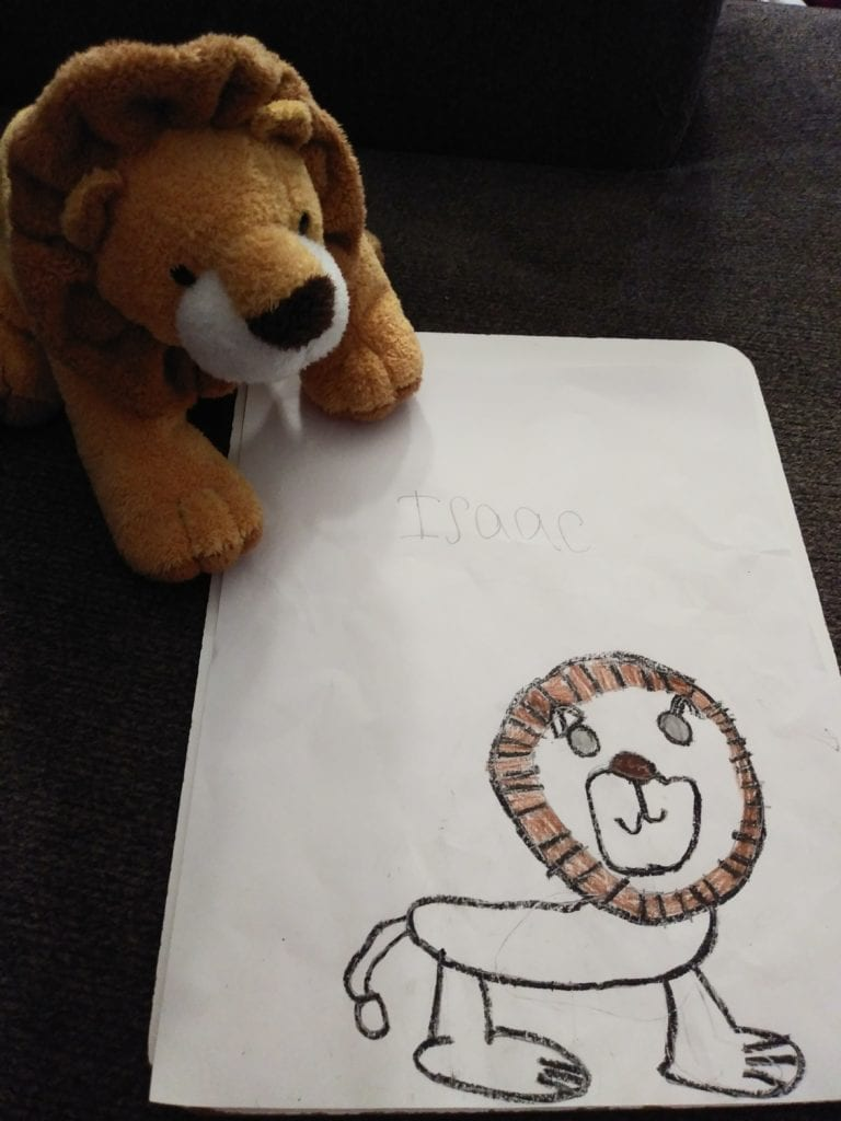 a lion stuffed animal and a drawing of the stuffed animal