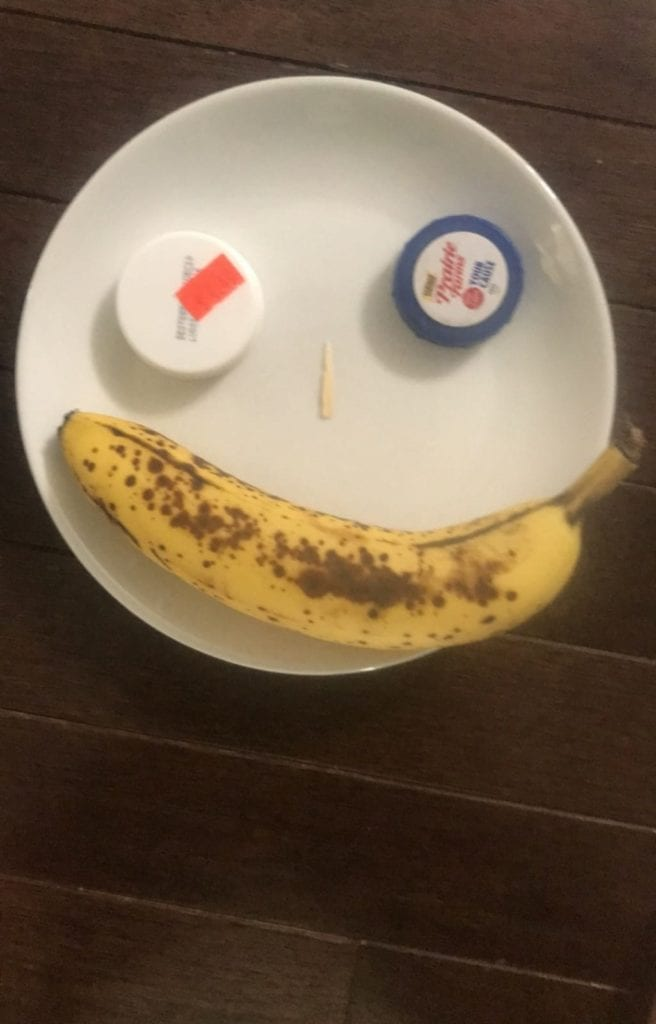 face made from a banana and caps on a plate