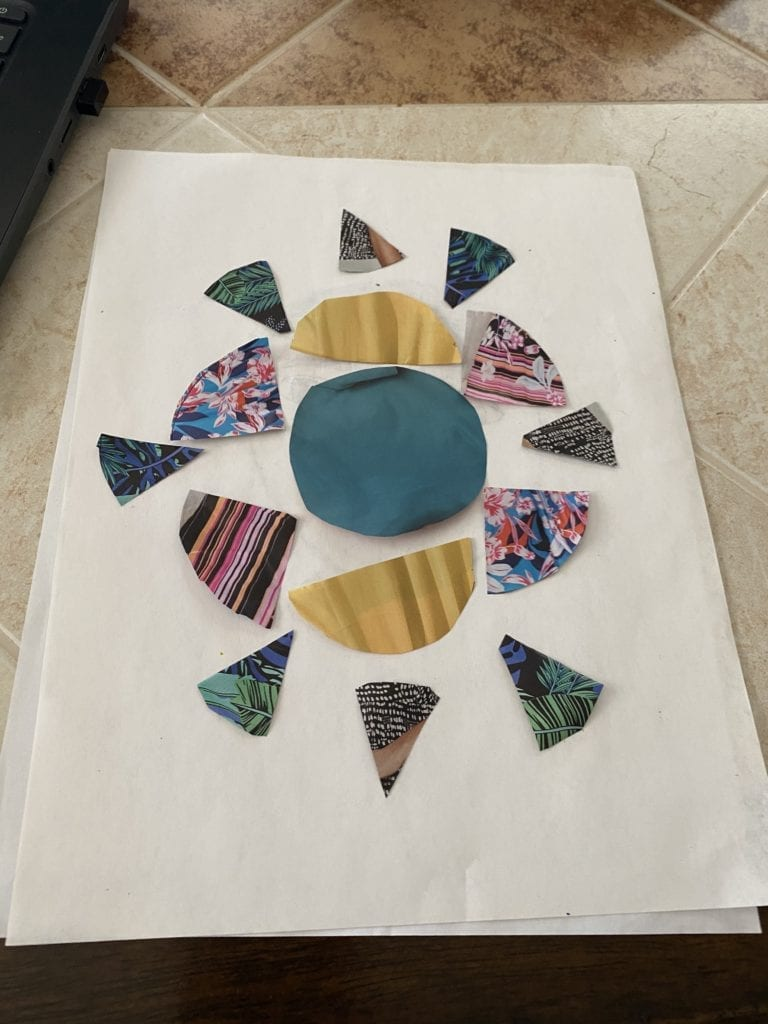 circles and pieces cut form a magazine and arranged in a design on a white paper