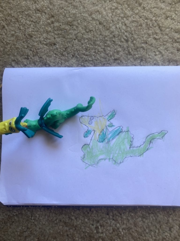 drawing of a dragon next to a toy dragon