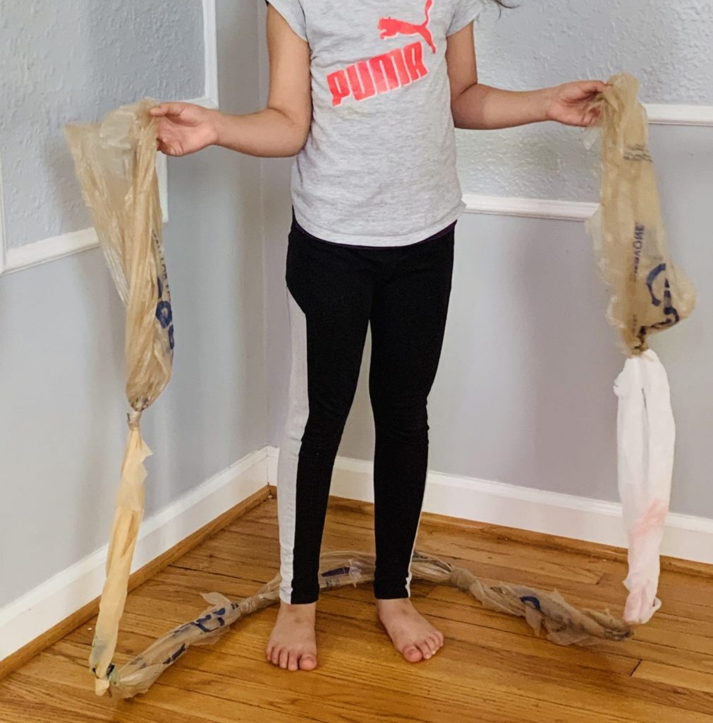 girl holding a plastic bag jump rope