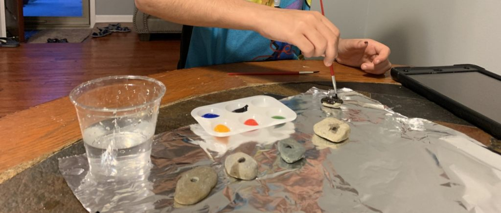 student hands painting rocks