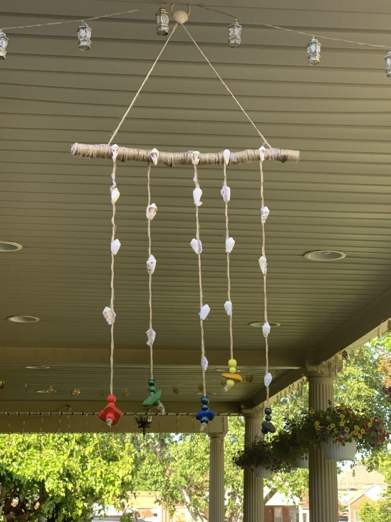 a mobile made from shells, string, and a stick