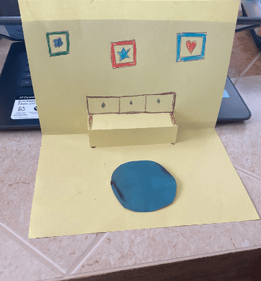 paper folded to look like a room with pop out chairs and a table
