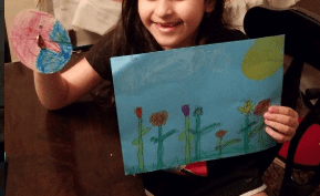 girl holding a coin spinner and a flower drawing
