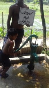 A child pumping water out of a water pump while an adult is holding a sign that reads Amal And Naju.