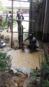 A couple of men working on building a water well.