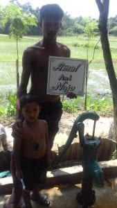 A child and adult holding the water well sign that reads Amal and Naju.