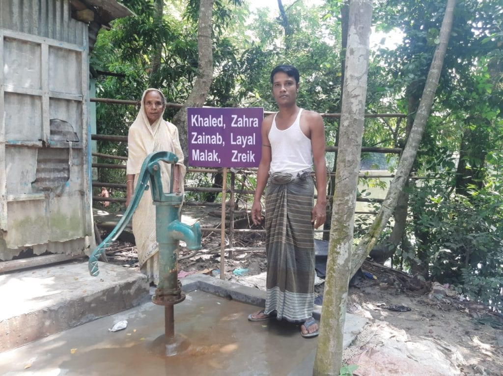 Picture of water well and sign with two individuals standing next to the sign.