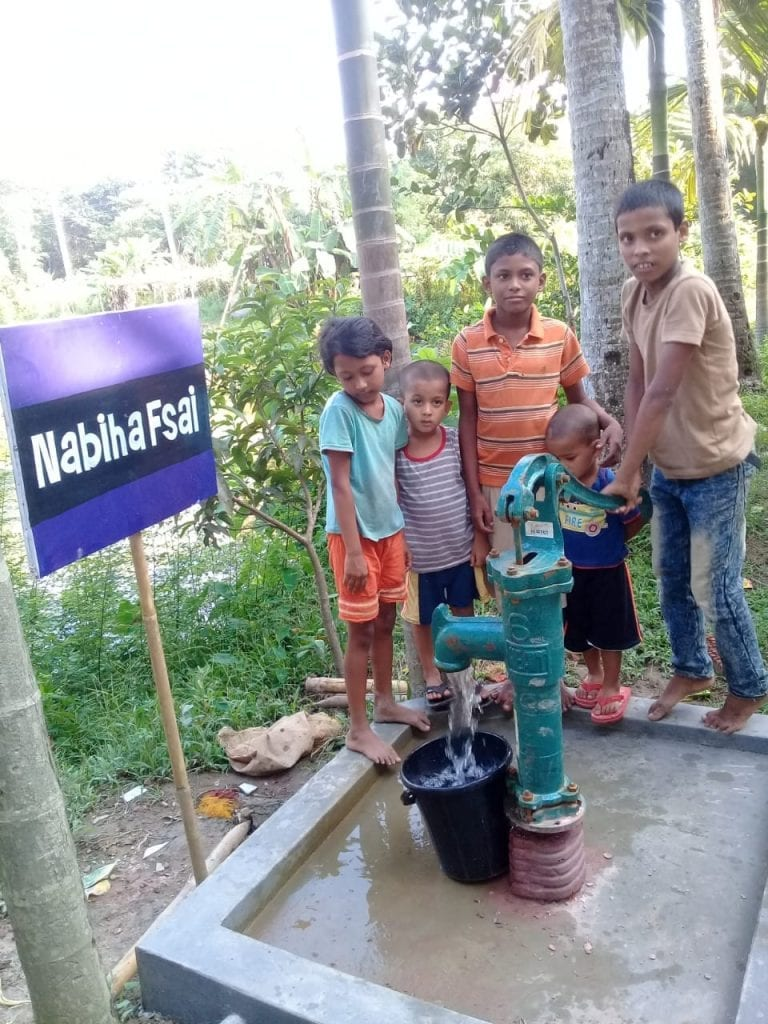 Picture of children pumping water out of water well.