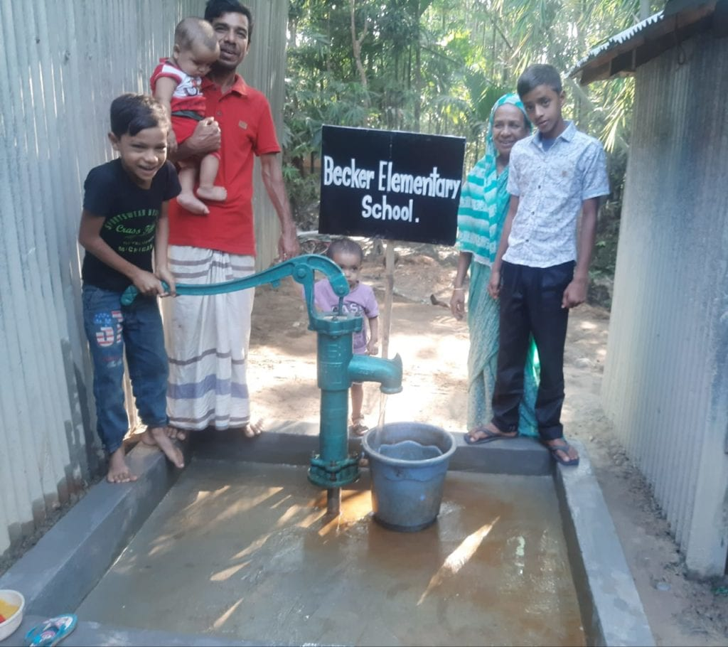 Picture of water well in Bangladesh with a Bengali family standing behind it.