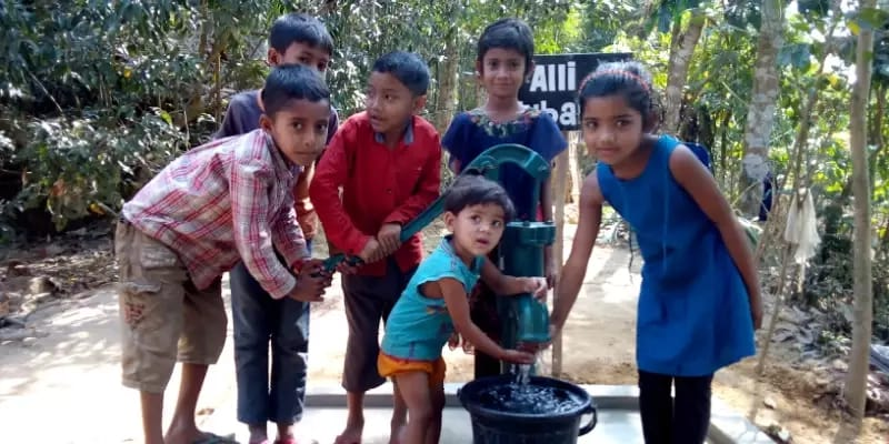 kids pumping water out of a water well