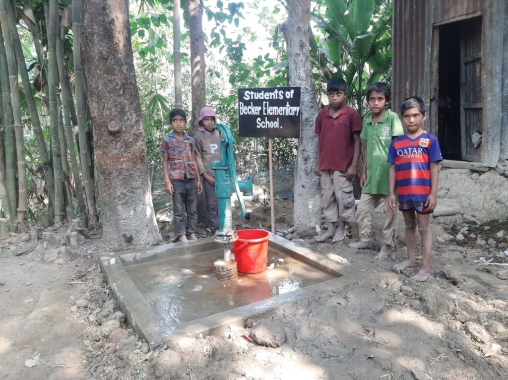Kids standing next to a water well