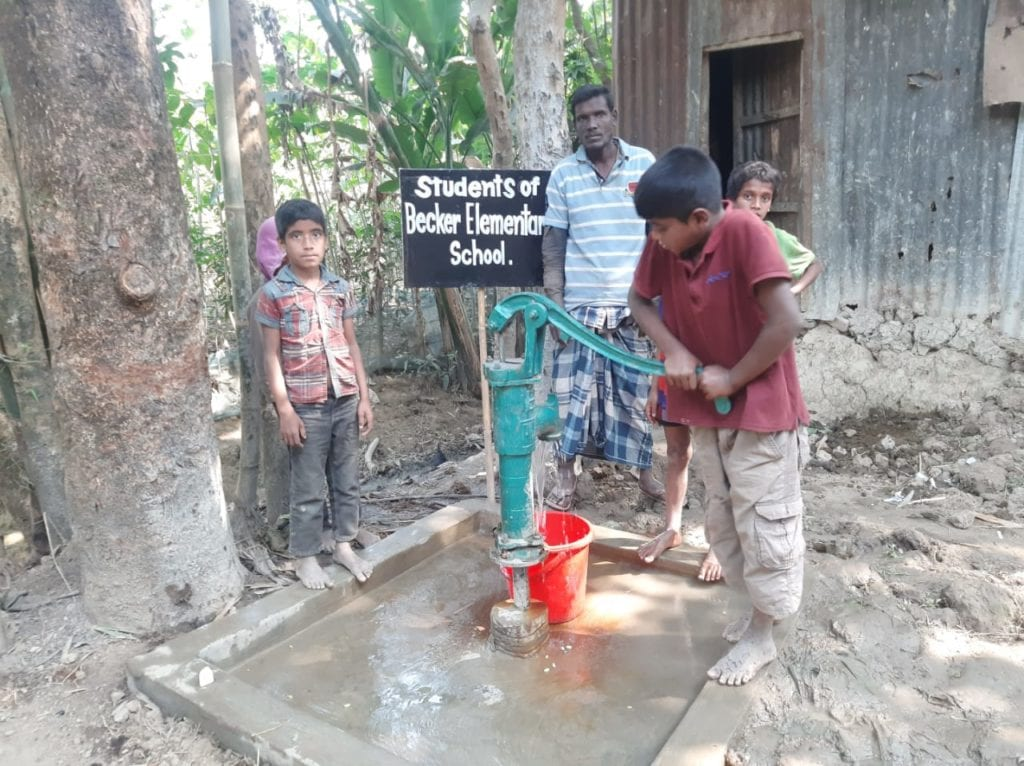 kids pumping water out of water well