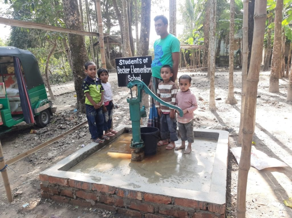 little children and a man standing next to a water well