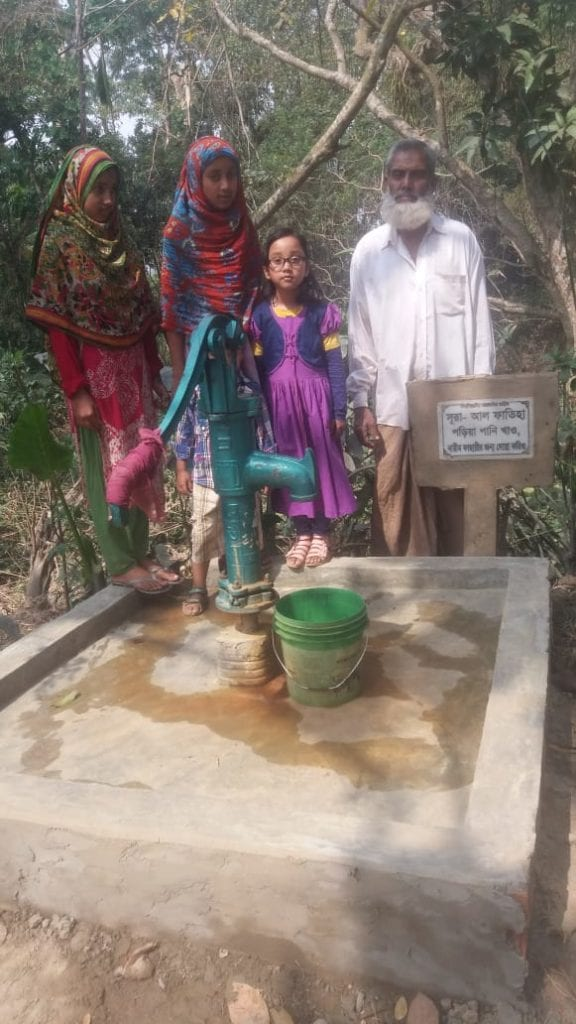 a family standing next to a water well