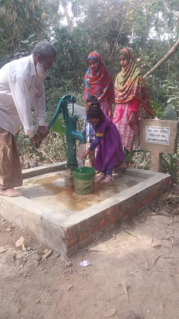 a family pumping water out of a water well