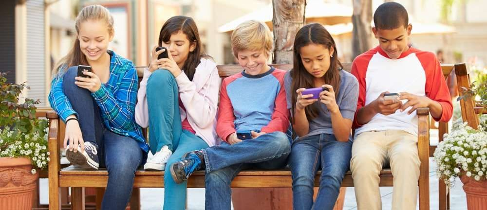 The picture shows 5 middle schoolers on a bench ignoring each other and engaged with their phones.