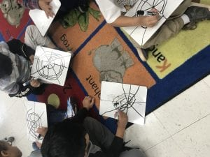 several students drawing spider webs on individual white boards