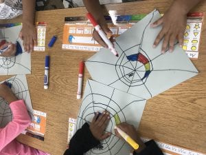 student hands coloring with red, yellow, and blue, inside of their spider web drawings