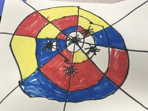 student artwork; a black spider web that has primary colors colored in between the spider web lines