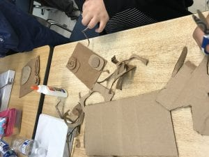 student hands cutting shapes out of cardboard