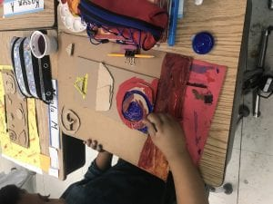 student hands painting a cardboard artwork with red and blue; the cardboard has several different shapes glued to it.