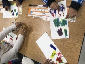student hands mixing colors on a white paper