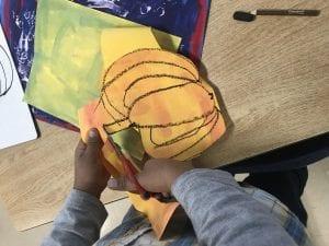 student hands cutting out an orange pumpkin