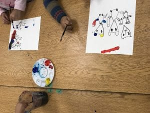 students' hands painting; the primary color paints are in the center with a cup of water