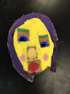 student made mask that is colorful and has a yellow face and purple hair