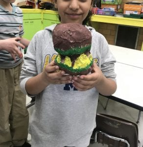 This artist is holding her paper mache hamburger that she painted the top and bottom of brown to look like a bun and then dark brown for meat in the middle and yellow and green peaking out for cheese and lettuce